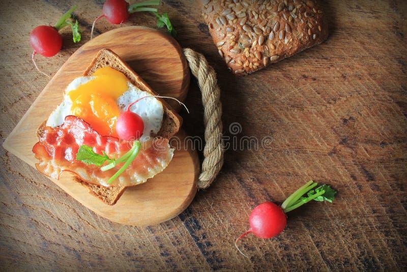 Caf? da manh?, bacon fri?vel, ovos fritos e p?o Sandu?che na placa de estaca Tabela r?stica Vista superior fotografia de stock
