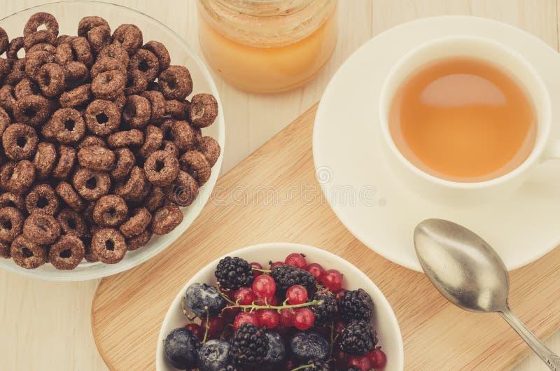 caf? da manh? com flocos, bagas, mel e um copo do ch?/caf? da manh? com flocos, bagas, mel e um copo do ch? Vista superior imagens de stock