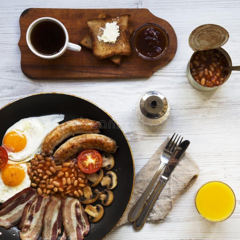 Caf? da manh? ingl?s completo em uma bandeja com ovos fritos, bacon, feij?es, salsichas e brindes na superf?cie de madeira branca imagem de stock royalty free