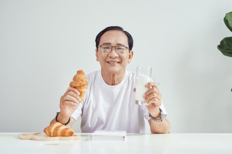 Caf? da manh? na manh? Croissant da terra arrendada da pessoa mais idosa com vidro do leite Alimento saud?vel fotos de stock