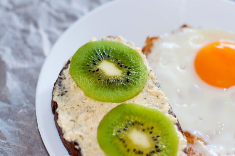 Caf? da manh? saud?vel e saboroso, sandu?che do p?o wholemeal com quivi e um ovo frito em uma placa branca, close-up, vista super foto de stock royalty free