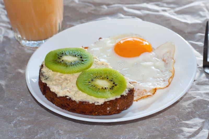 Caf? da manh? saud?vel e saboroso, suco, sandu?che wholegrain com quivi e ovo frito na placa branca imagem de stock royalty free