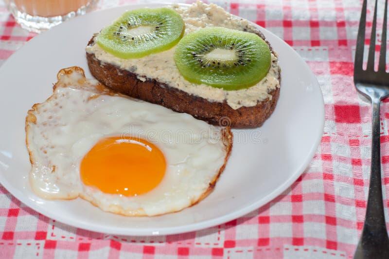 Caf? da manh? saud?vel, saboroso, suco do marmelo, sandu?che do quivi da inteiro-gr?o e ovo frito em uma placa branca imagem de stock