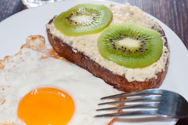 Caf? da manh? saud?vel, saboroso, suco, sandu?che do p?o da inteiro-gr?o, quivi e ovo frito em uma placa branca, na tabela de mad fotos de stock