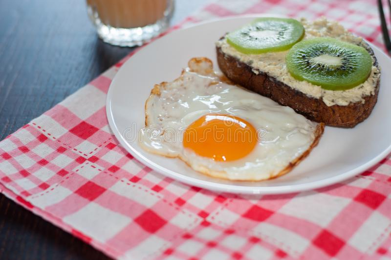 Caf? da manh? saud?vel, saboroso, suco, sandu?che do p?o wholemeal com quivi e um ovo frito na placa branca fotos de stock