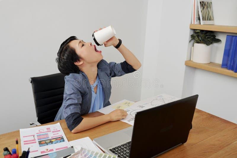 Caf? de consumici?n de la mujer en la oficina imagen de archivo libre de regalías