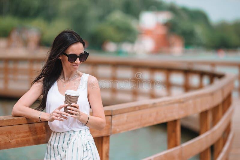 Caf? de consumici?n de la mujer urbana joven feliz en ciudad europea foto de archivo libre de regalías