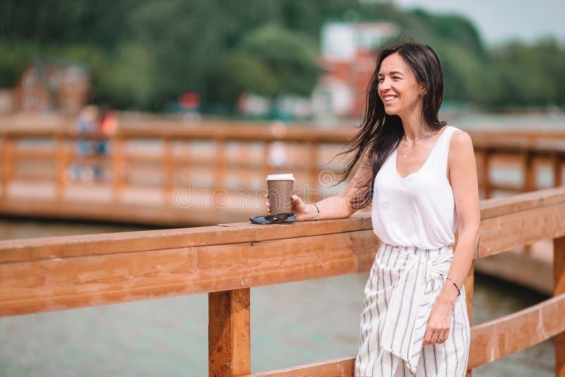 Caf? de consumici?n de la mujer urbana joven feliz en ciudad europea fotos de archivo libres de regalías