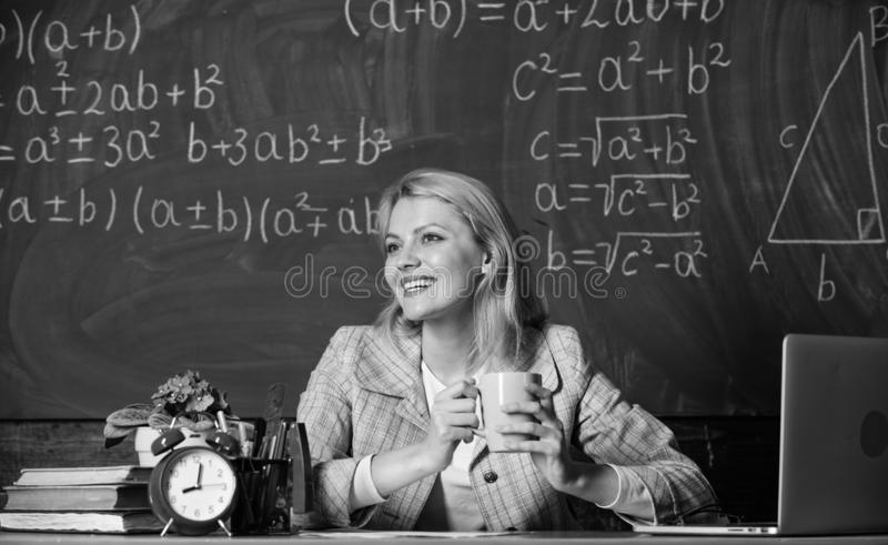 Caf? de la bebida de la mujer en sala de clase profesor con el despertador en la pizarra Tiempo De nuevo a escuela D?a de los pro imagenes de archivo