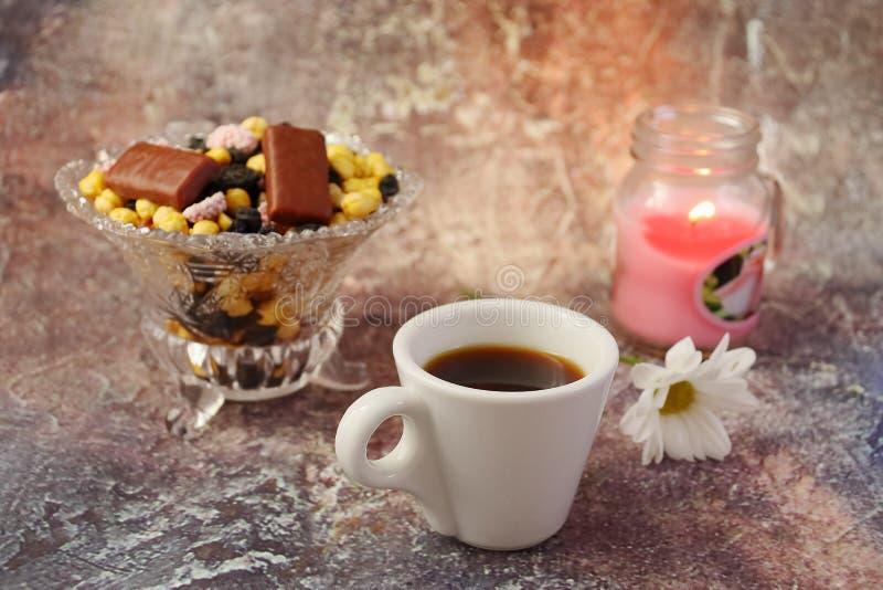 Caf? de matin press? : une tasse de caf?, de fleurs dans un vase, de fruits secs et de bonbons dans un vase, une bougie br?lante photo libre de droits