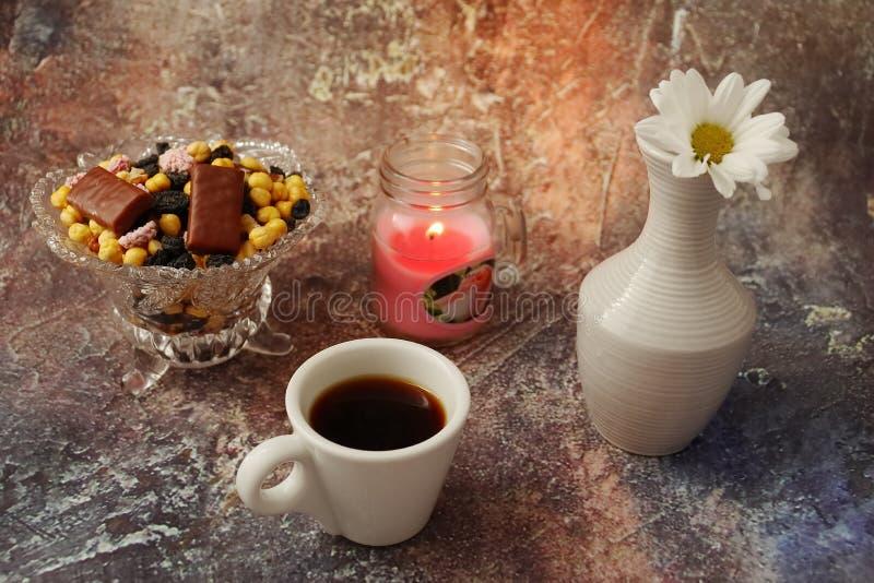 Caf? de matin press? : une tasse de caf?, de fleurs dans un vase, de fruits secs et de bonbons dans un vase, une bougie br?lante photographie stock