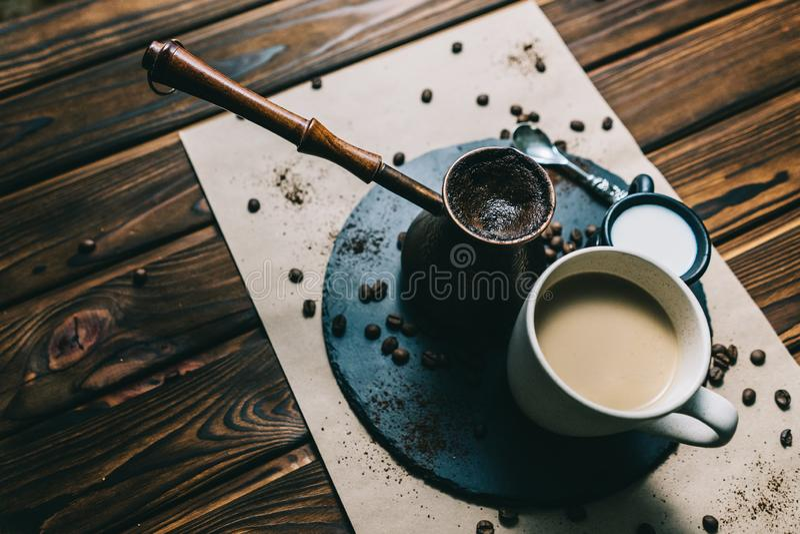 Caf? en un rallador con una taza en un fondo oscuro con crema fotos de archivo