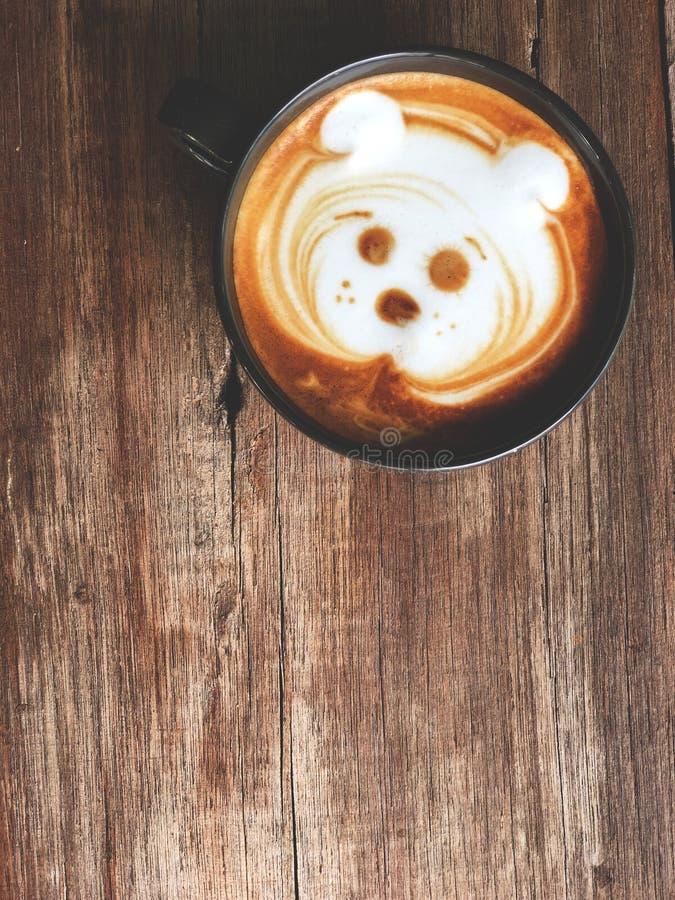 Caf? lindo del arte del latte de la cara del perro en la taza blanca en la tabla de madera foto de archivo