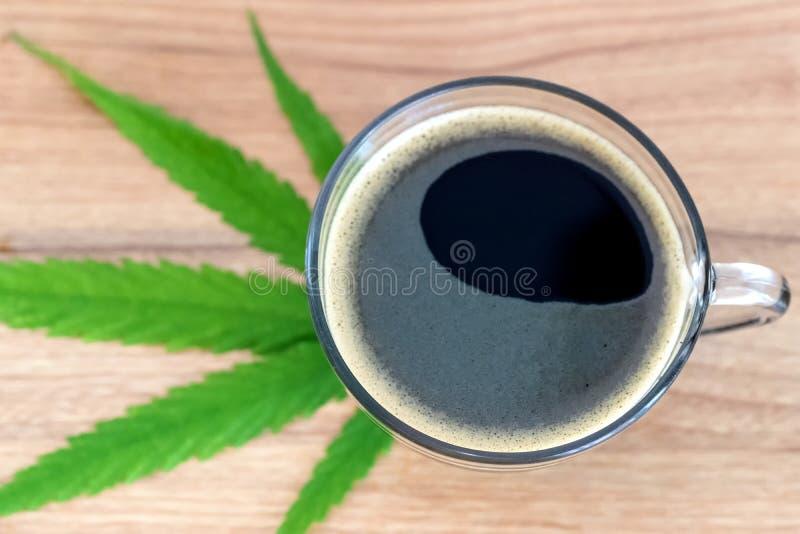 Caf? noir avec des feuilles de Cannabismarijuana photos stock