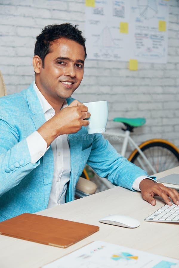 Caf? potable d'homme d'affaires sur le lieu de travail photo libre de droits