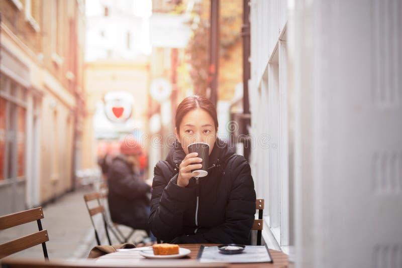 Caf? potable de belle femme asiatique avec le g?teau sur la table photographie stock