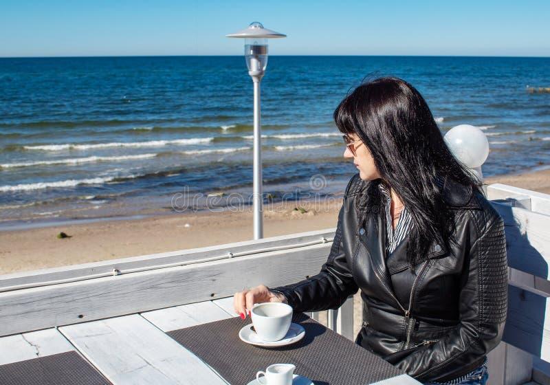 Caf? potable de jeune femme de brune dans un caf? ext?rieur pr?s de la mer images stock