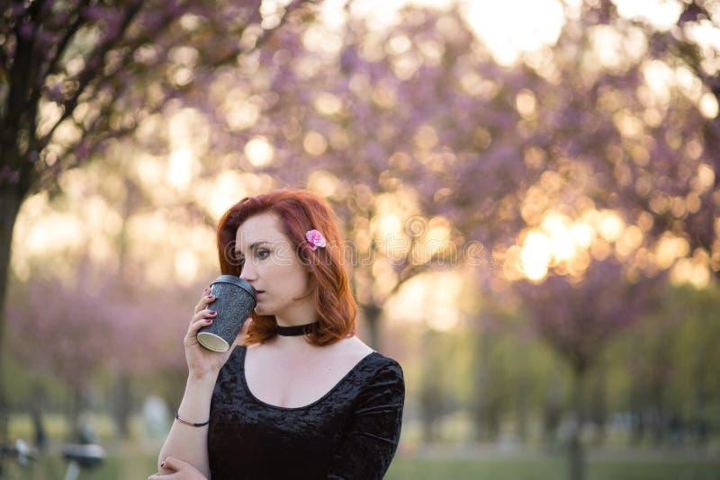 Caf? potable de la tasse de papier de tasse - jeune femme heureuse de danseur de voyage appr?ciant le temps libre en parc de fleu photo libre de droits