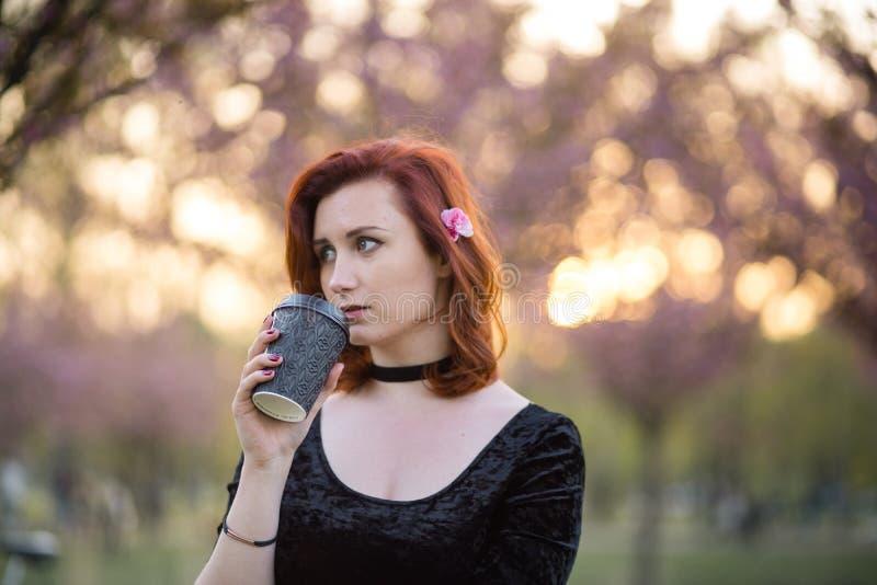 Caf? potable de la tasse de papier de tasse - jeune femme heureuse de danseur de voyage appr?ciant le temps libre en parc de fleu photographie stock