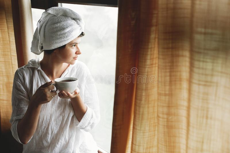 Caf? potable ou th? de belle jeune femme heureuse, se reposant ? la grande fen?tre en bois dans la chambre ? coucher de chambre d images libres de droits