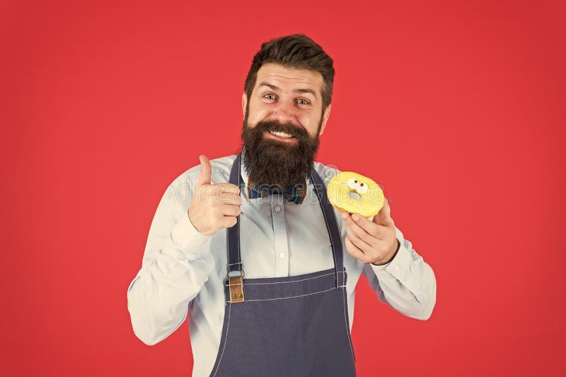 Cafe and bakery concept. Sweet donut from baker. Man bearded baker in cooking apron hold cute dessert. Ways to reduce royalty free stock photo