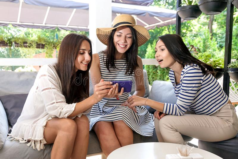 Cafe buy online girls mobile three phone young women internet digital white summer flowers cocktail happy dreen leaves brunette lo stock photo