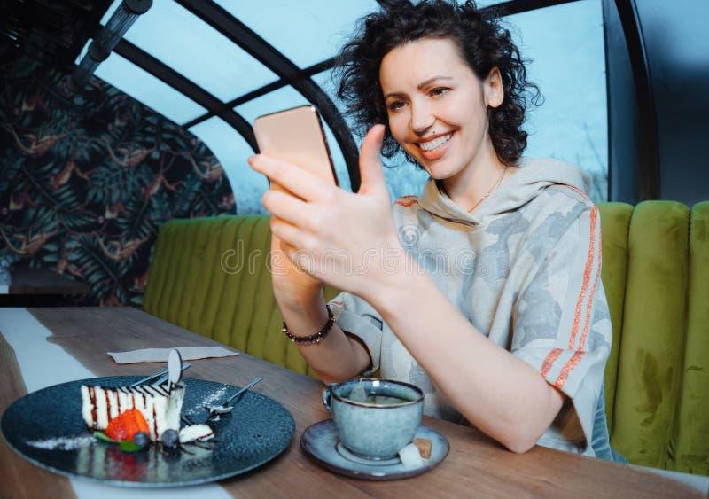Cafe City lifestyle kobieta na telefonie pijąca kawy SMS-y na smartfonie w modnej miejskiej kawiarni zdjęcia stock