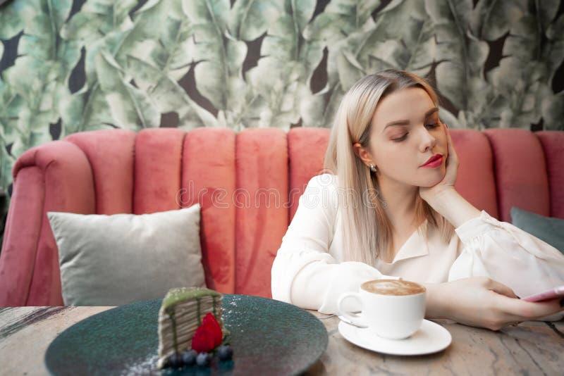 Cafe City lifestyle kobieta na telefonie pijąca kawy SMS-y na smartfonie w modnej miejskiej kawiarni zdjęcie royalty free