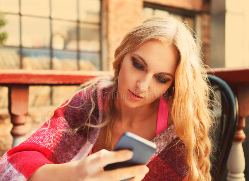 Cafe city lifestyle woman with mobile phone. Drinking coffee texting text message on smartphone sitting outdoor in cozy urban cafe stock photos