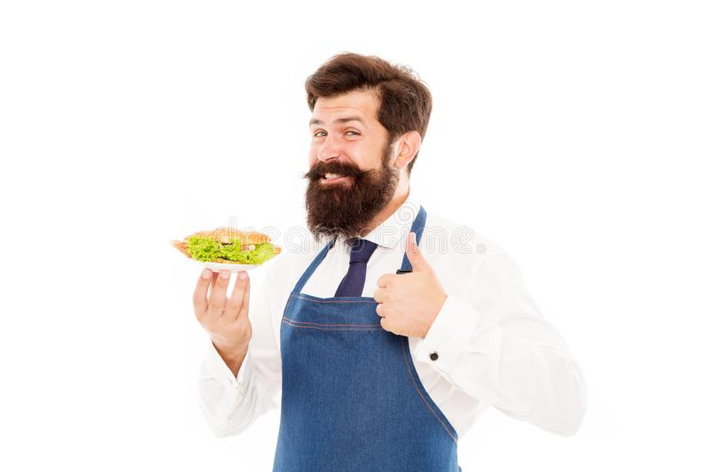 Cafe concept. Guy serving croissant stuffed with lettuce and fresh vegetables. Healthy food. Chef proud of croissant royalty free stock photo