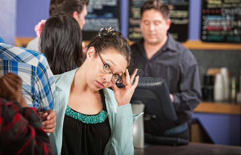 Cafe Customer with Headache. Annoyed cafe customer waiting in line to order royalty free stock image