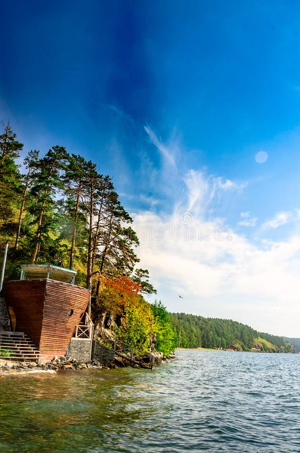 Cafe in the form of a ship hull on the shore of a large mountain lake royalty free stock photography