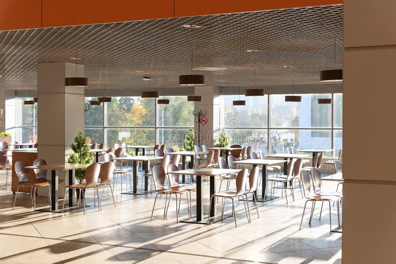 Cafe Interior. Modern cafe interior with bright room with tables and chairs nobody, large windows, modern style royalty free stock photo