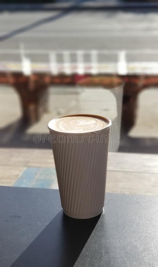Cafe Latte with Heart Design in White Striped Coffee Cup. Delicious café latte drink served in a white paper cup with raised stripes that act as a cool royalty free stock photo