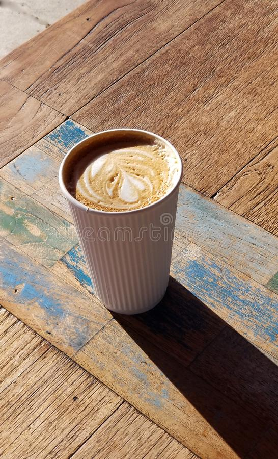 Cafe Latte with Heart Design in White Striped Coffee Cup. Delicious café latte drink served in a white paper cup with raised stripes that act as a cool stock photo