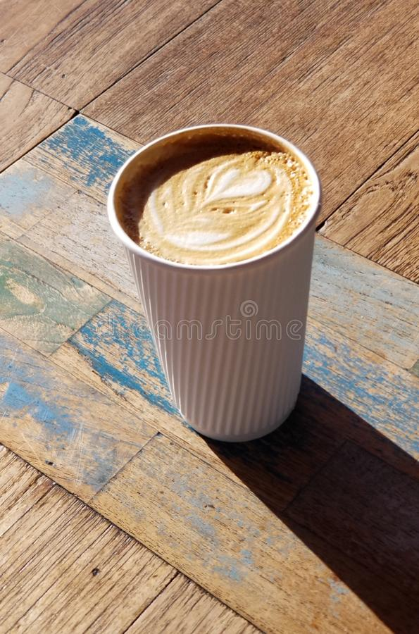 Cafe Latte with Heart Design in White Striped Coffee Cup. Delicious café latte drink served in a white paper cup with raised stripes that act as a cool royalty free stock photography