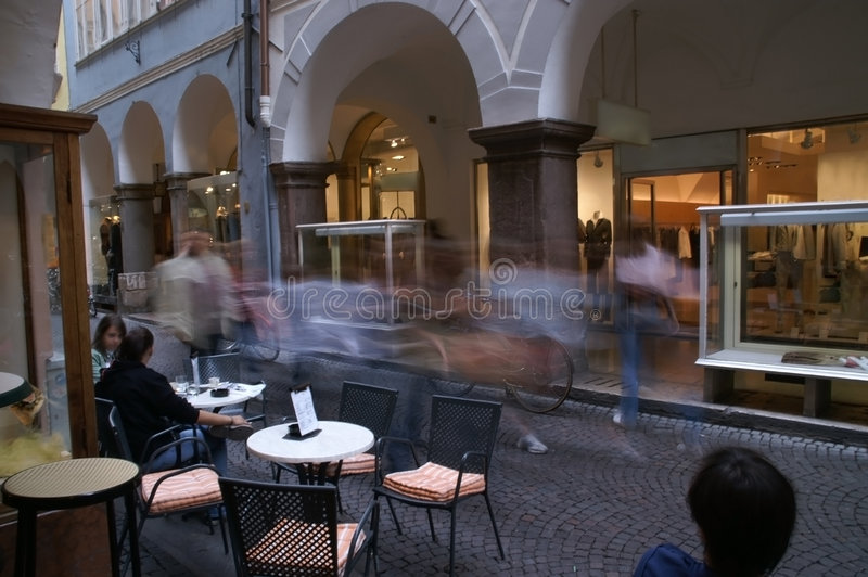 Cafe by mall 1. This picture shows a street scene in the old part of town of Meran (Italy). A long exposure time let humans going past smear. The sitting people