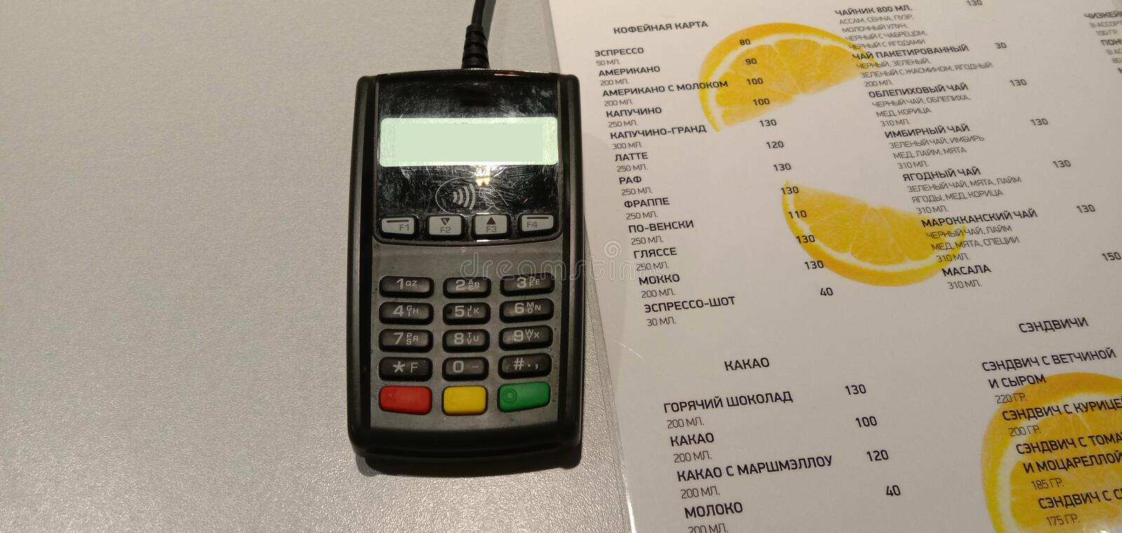 Cafe menu with prices and a list of drinks and a reader of electronic, payment cards. Close-up stock photo