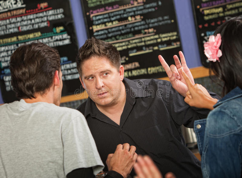 Cafe Owner with Rude Customer. Cafe owner talking with rude customers in line royalty free stock photography