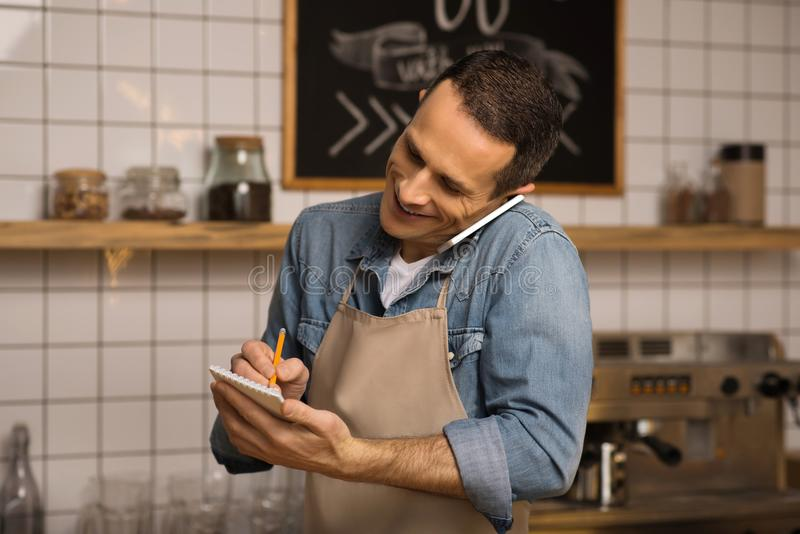 Cafe owner taking notes. Confident smiling cafe owner taking notes and talking on smartphone royalty free stock photos