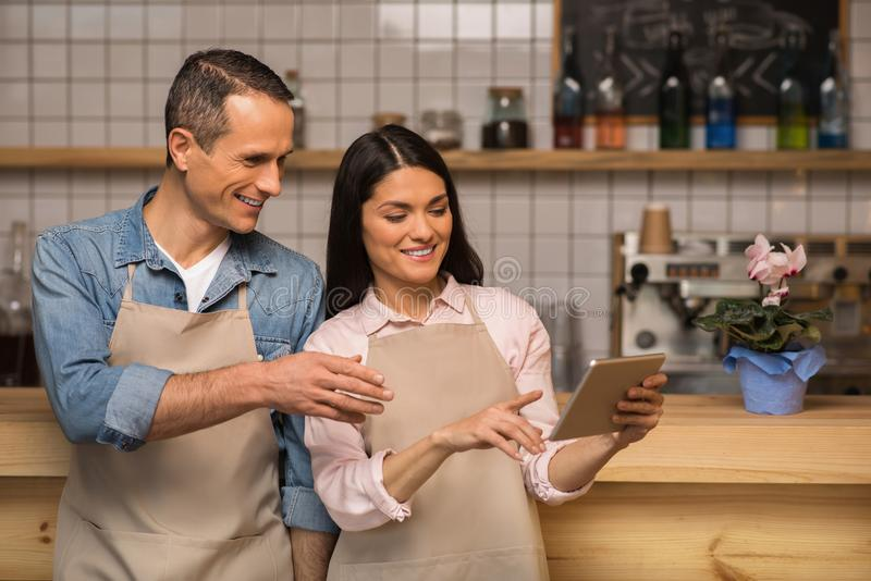 Cafe owners using digital tablet. Couple of cafe owners using digital tablet and talking in coffee shop stock image