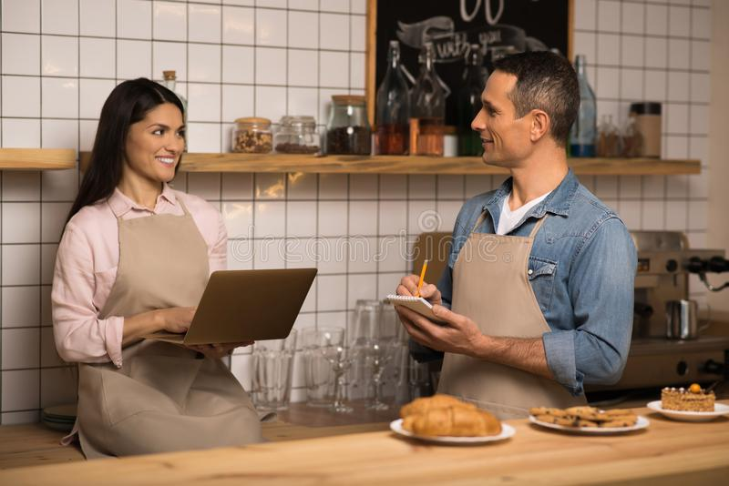 Cafe owners using laptop. Young couple of cafe owners using laptop and smiling each other stock photography