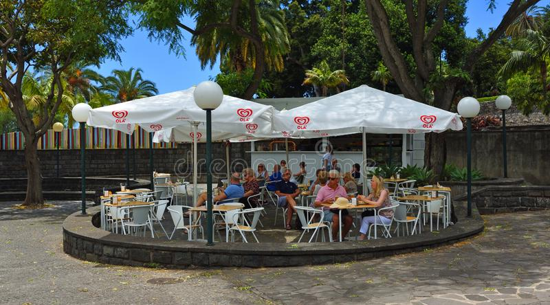 Cafe in the park with chairs tables and parasols. royalty free stock photography