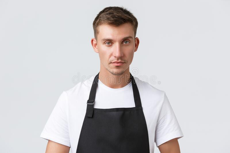 Cafe and restaurants, coffee shop owners and retail concept. Close-up of handsome waiter serving tables, taking client royalty free stock photo