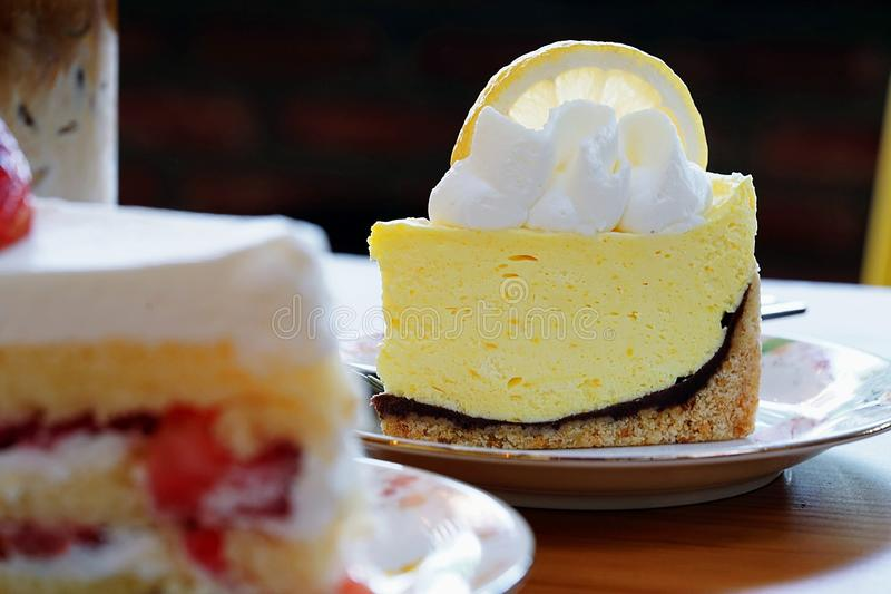 A cafe Scene for background. Two delicious cakes on wooden table, close up lemon meringue pie royalty free stock photos