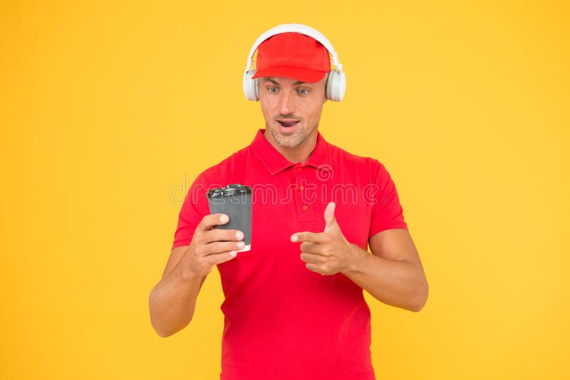 Cafe stuff red uniform with cap serving coffee yellow background. Man recommend to try drink. Hot beverage. Here is your stock images