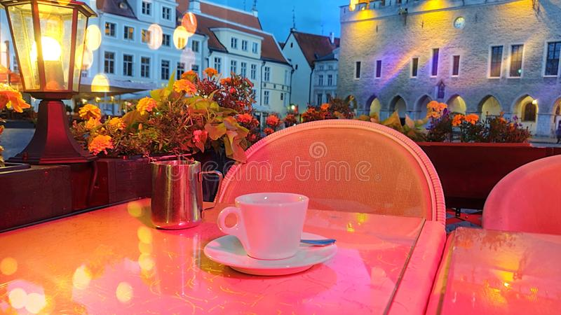 Cafe table street cafe cup of coffee evening city light blurring bokeh evening city flowers hose medieval town lifestyle dinner  t. Cafe table street cafe cup of royalty free stock photos