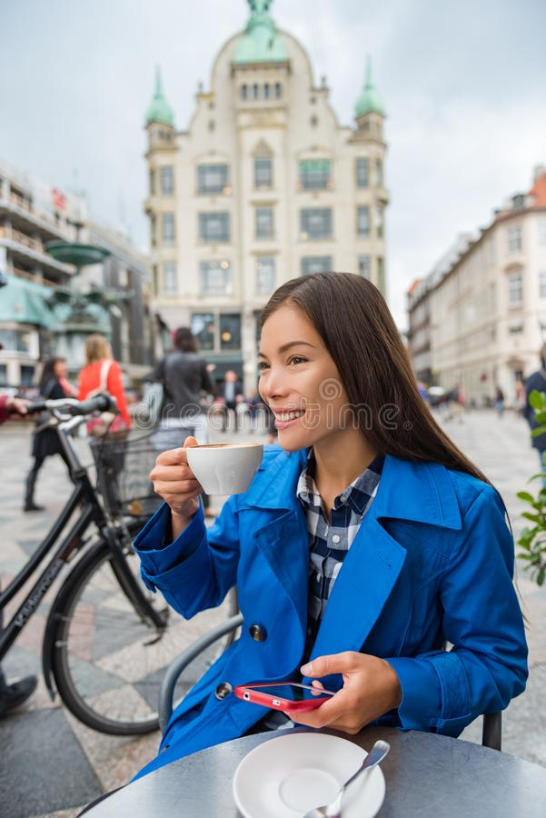 Cafe woman drinking cappuccino coffee at outdoor street terrace in European city. Europe travel lifestyle. Asian businesswoman in. Cafe woman texting sms on stock images