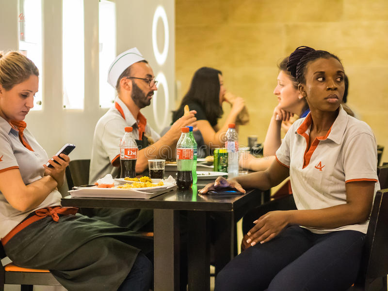 Cafe workers take a break, Paris. Cafe workers in uniform take a break in food court at the Carrousel du Louvre, Paris, France stock photo