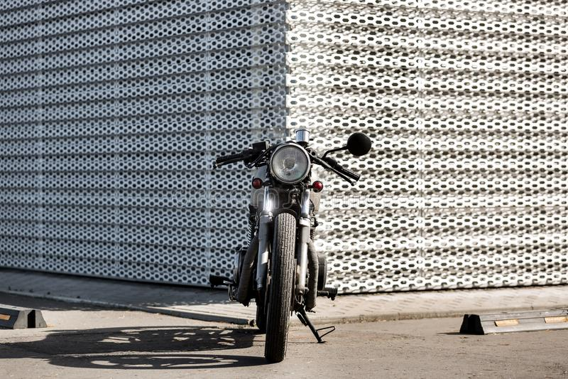 Vintage motorcycle cafe racer style. Caferacer motorcycle parking near wall of finance building. Everything is ready for having fun after hard day in office royalty free stock images